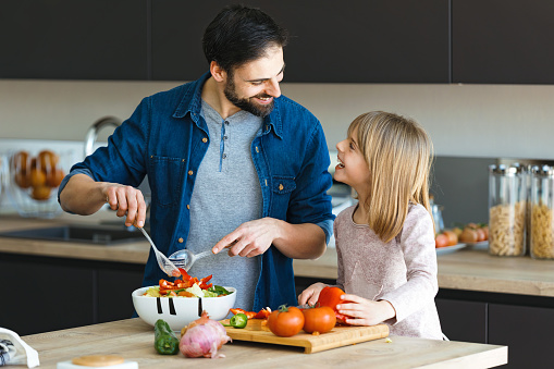 Shot of attractive young man with her little cute daughter making salad together on kitchen at home