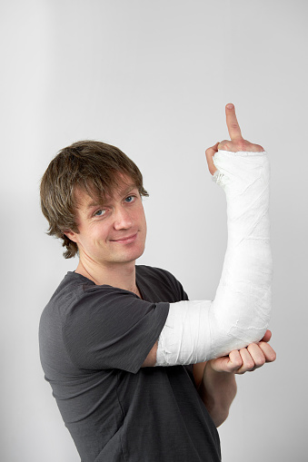 istock Attractive young man with plaster cast on his hand showing sing fuck you on a white wall background. 1272237910