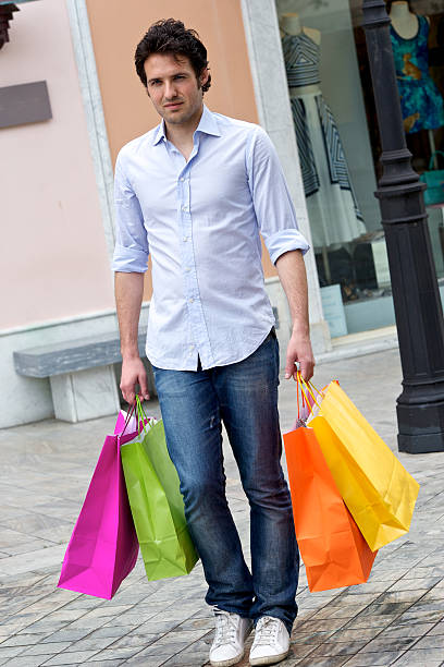 Attraktiver junger Mann mit shopping Taschen – Foto