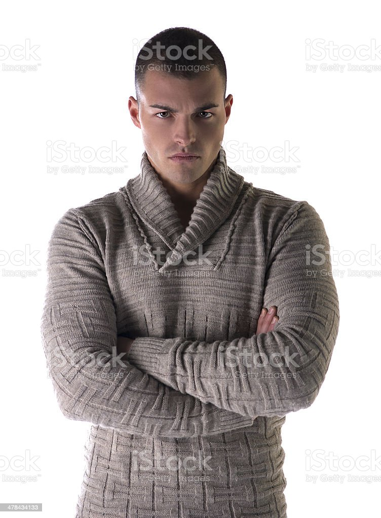 Attractive young man with stern, severe expression, arms crossed stock photo