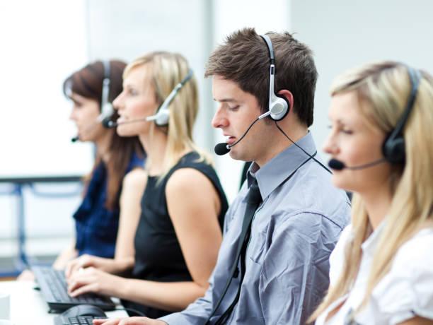attraktive junge mann arbeitet in einem callcenter - möbel 24 online stock-fotos und bilder
