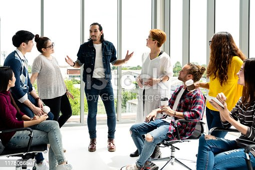 istock Attractive young multiethnic group talking at relax zone in coffee break time at office. Young asian hipster man sharing lifestyle idea to staff friends with fun and happy in happy workplace concept. 1178086867
