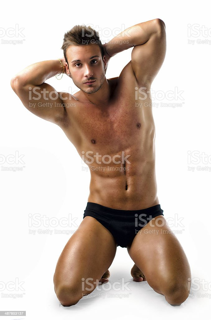 Attractive young muscular man posing on his knees stock photo