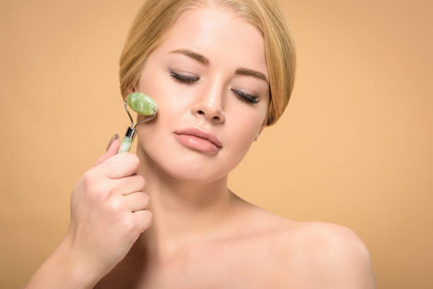 attraktive junge nackte Frau massieren Gesicht mit jade Roller und blickte isoliert auf beige – Foto