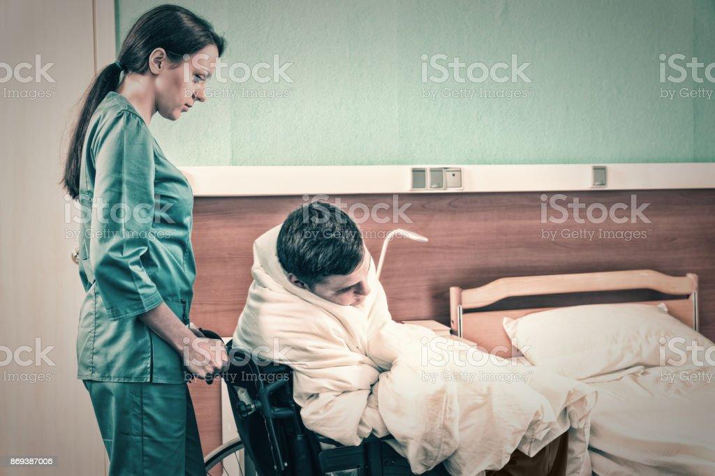 Atractivo joven enfermera en uniforme, tirando la silla de ruedas con enfermo cubierto con tejido en sala de hospital - foto de stock