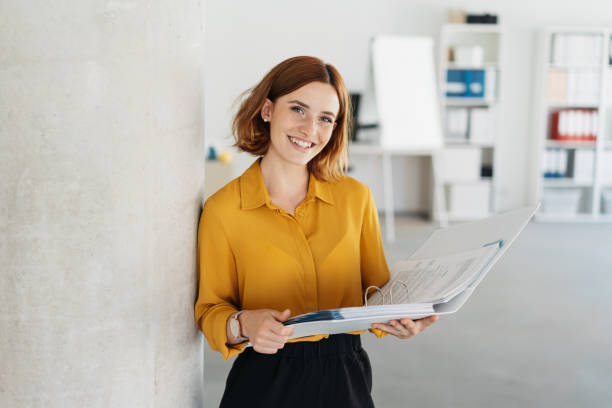 Attractive young office worker holding large file stock photo