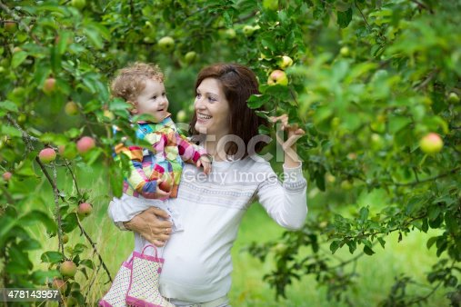 istock Attractive young pregnant woman holding her daughter under apple tree 478143957