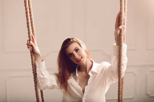 Attractive young redhead woman with long hair sitting on swing in man's shirt stock photo