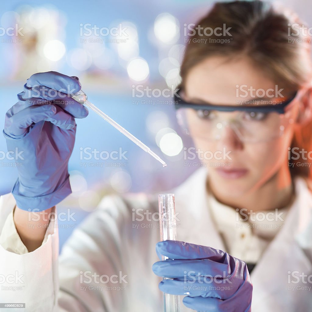 Attractive young scientist pipetting. stock photo