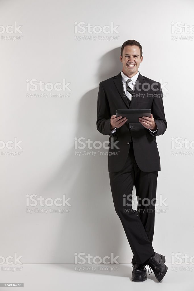 Attractive young smiling businessman with a digital tablet royalty-free stock photo