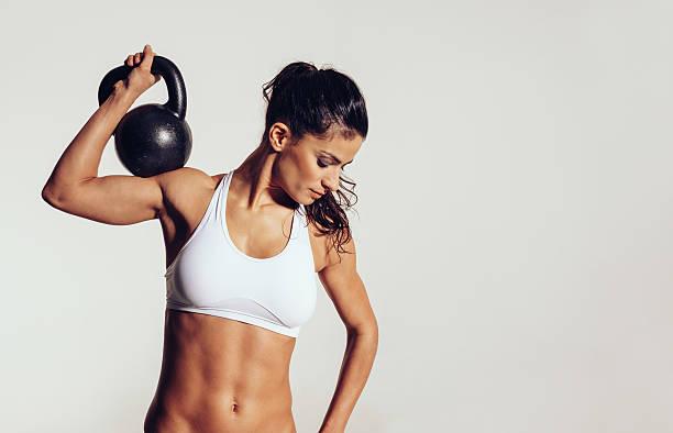 atractiva joven haciendo ejercicios con crossfit - pesa rusa fotografías e imágenes de stock