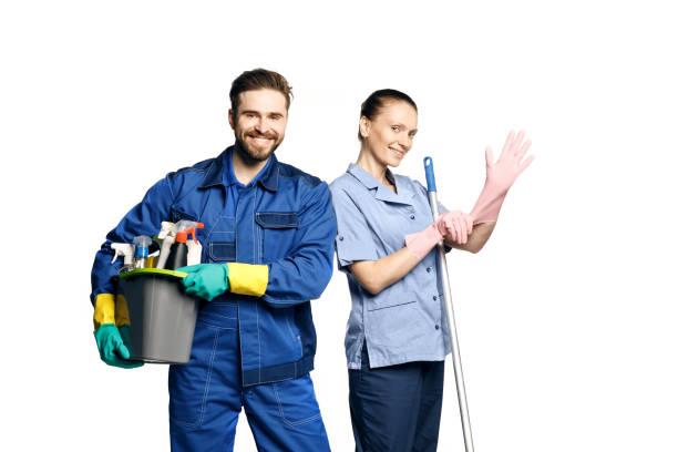 attraktive junge frau und mann in reinigungsuniform und gummihandschuhen mit besenreinigungsmitteln in den händen - hausmeister stock-fotos und bilder