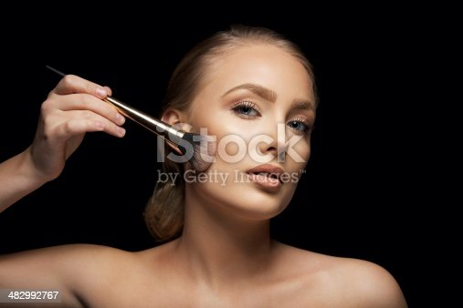istock Attractive young woman applying make up 482992767