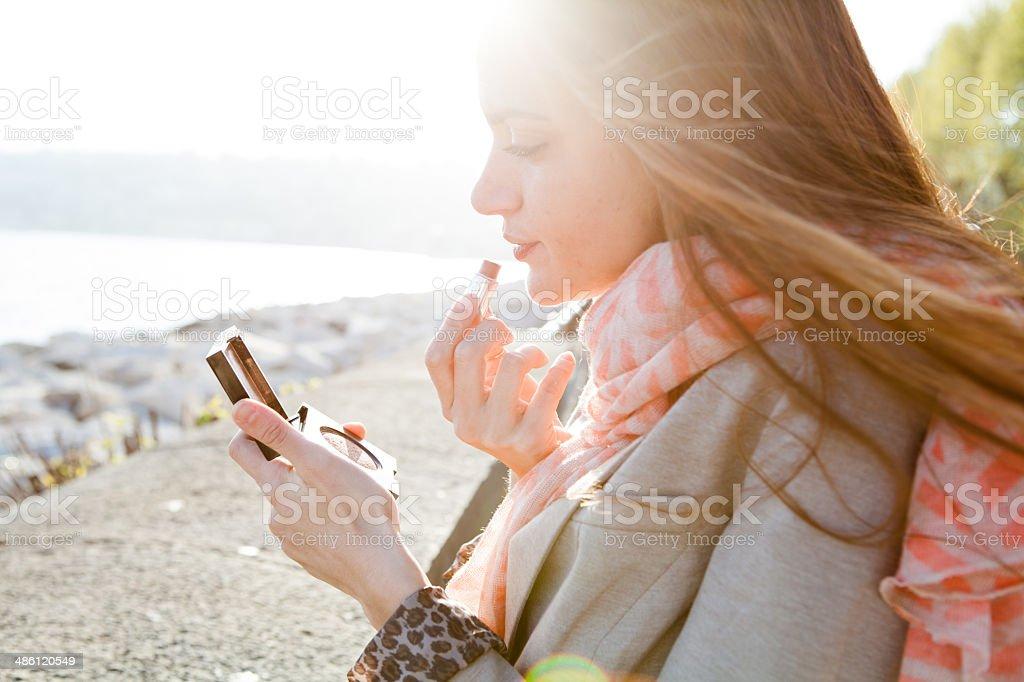 Attraente giovane donna di applicare il rossetto rosso, guardando in uno specchio - foto stock