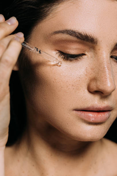 attractive young woman applying serum on face with pipette - mettersi lo smalto foto e immagini stock