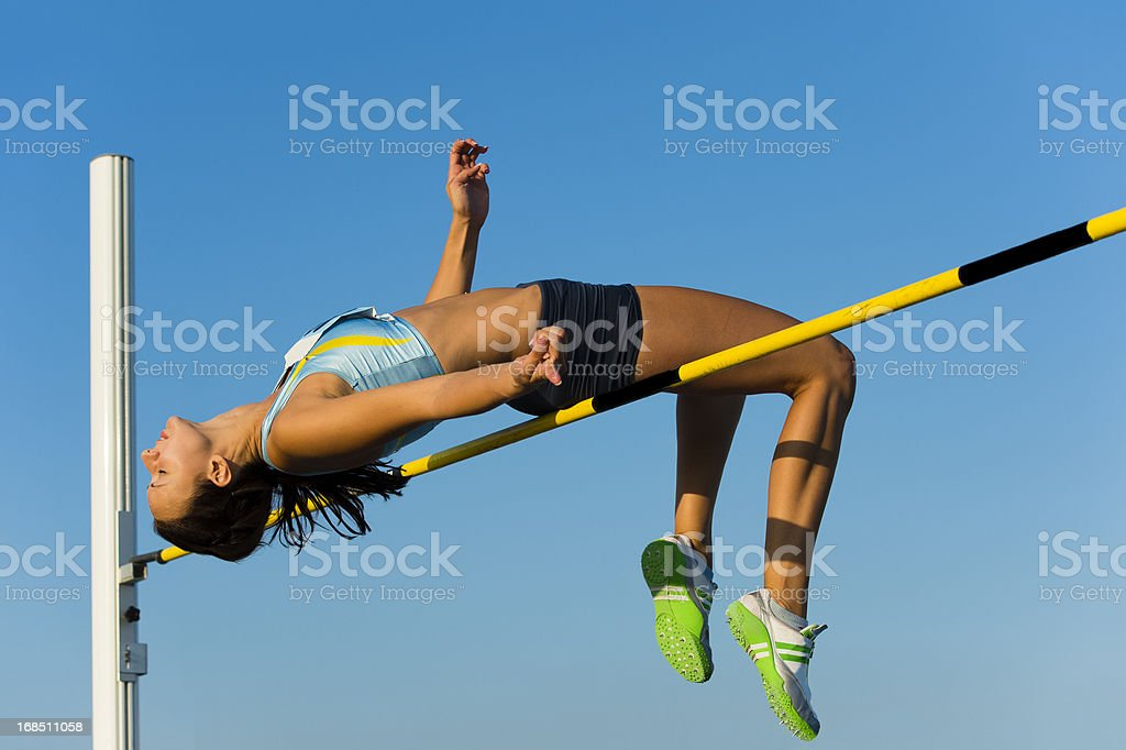 Attractive young woman at high jump stock photo