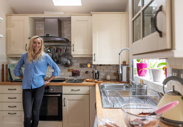 Attractive young woman at home in the kitchen with baking equipment stock photo