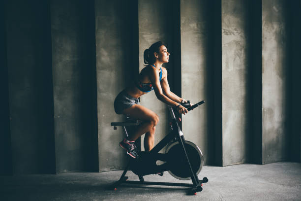 Attractive young woman at the gym riding on exercising bike. stock photo