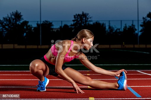 istock Attractive young woman athlete stretching legs on stadium 857430452