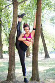 Attractive young woman athlete warming up stretching her muscles before starting her workout in a park