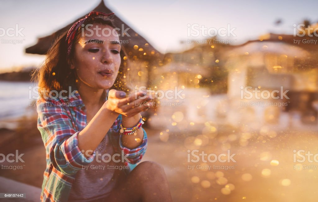 Attractive young woman blowing glitter at beach in the summer stock photo