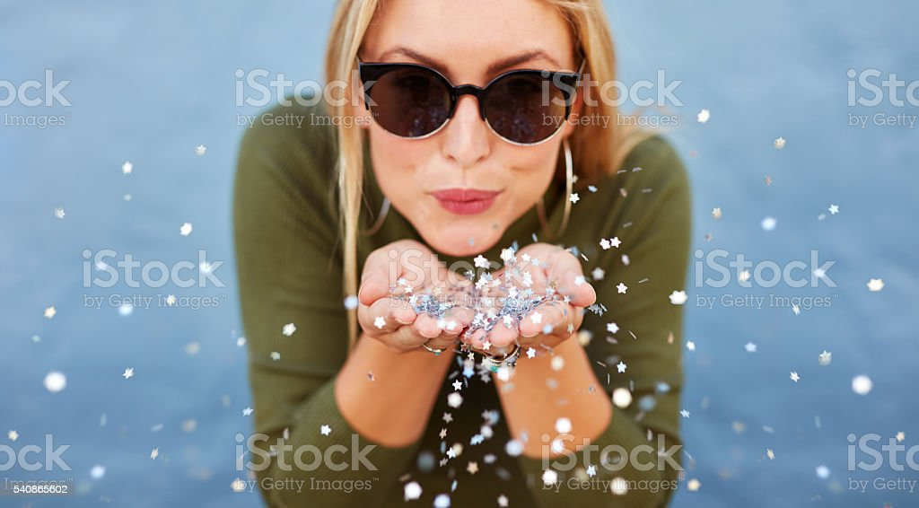 Attractive young woman blowing glitters Close up portrait of attractive young woman blowing glitters. Caucasian Female model having fun over blue background. Women Stock Photo
