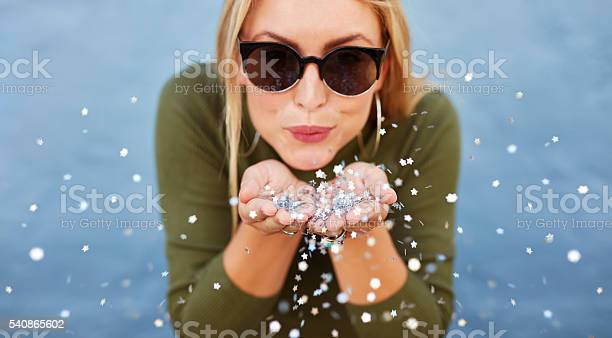 Attractive Young Woman Blowing Glitters Stock Photo - Download Image Now