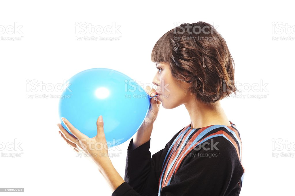 Attractive Young Woman Blowing Up a blue Balloon stock photo