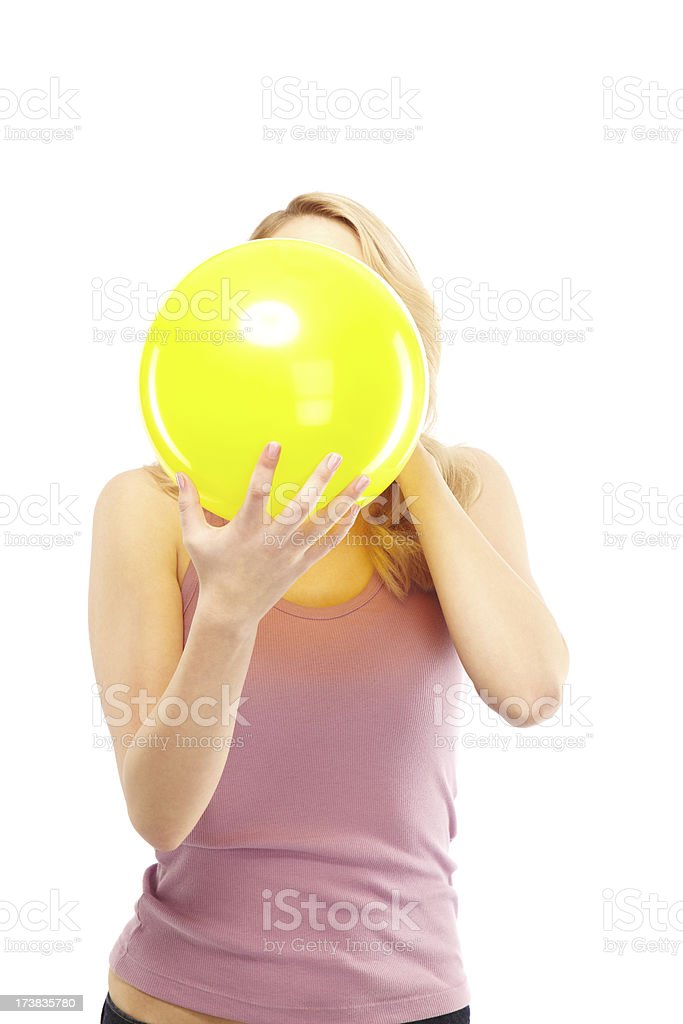 Attractive Young Woman Blowing up a Yellow Balloon. Isolated. stock photo