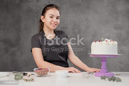 istock Attractive young woman brunette confectioner presents a white cake with small red flowers of a food rose. 1154983643