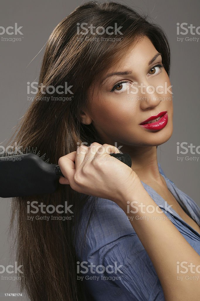 Attractive Young Woman Brushing Her Hair royalty-free stock photo