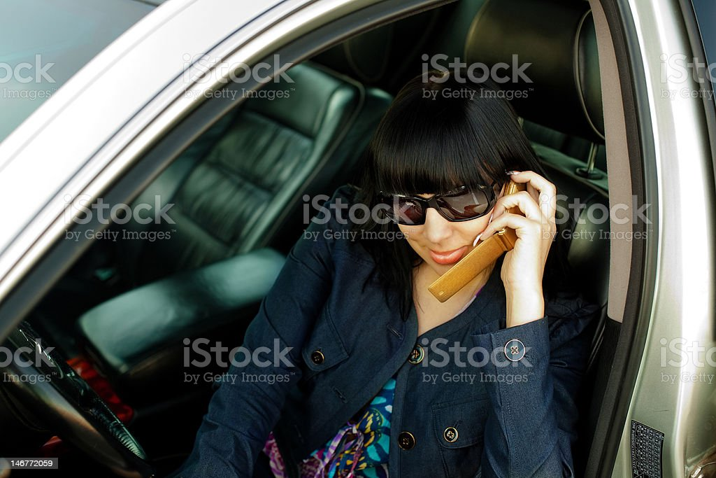 Attractive young woman calling by cellular phone in car royalty-free stock photo