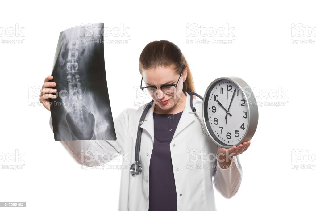 Attractive young woman doctor with clock in her hands with x-ray making diagnosis in white uniform on white background stock photo