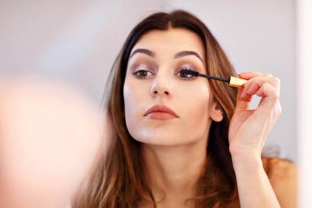 Attraktive junge Frau Make-up beim Betrachten des Spiegels im Bad zu tun – Foto