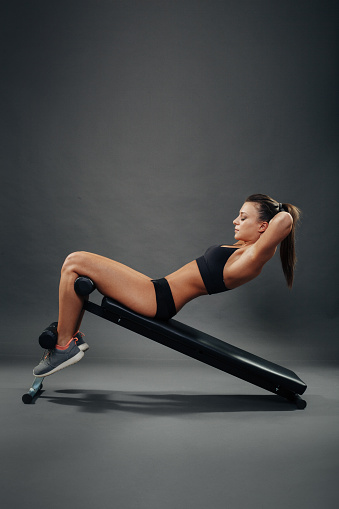 629605142 istock photo Attractive young woman doing sit ups on incline bench 483878614