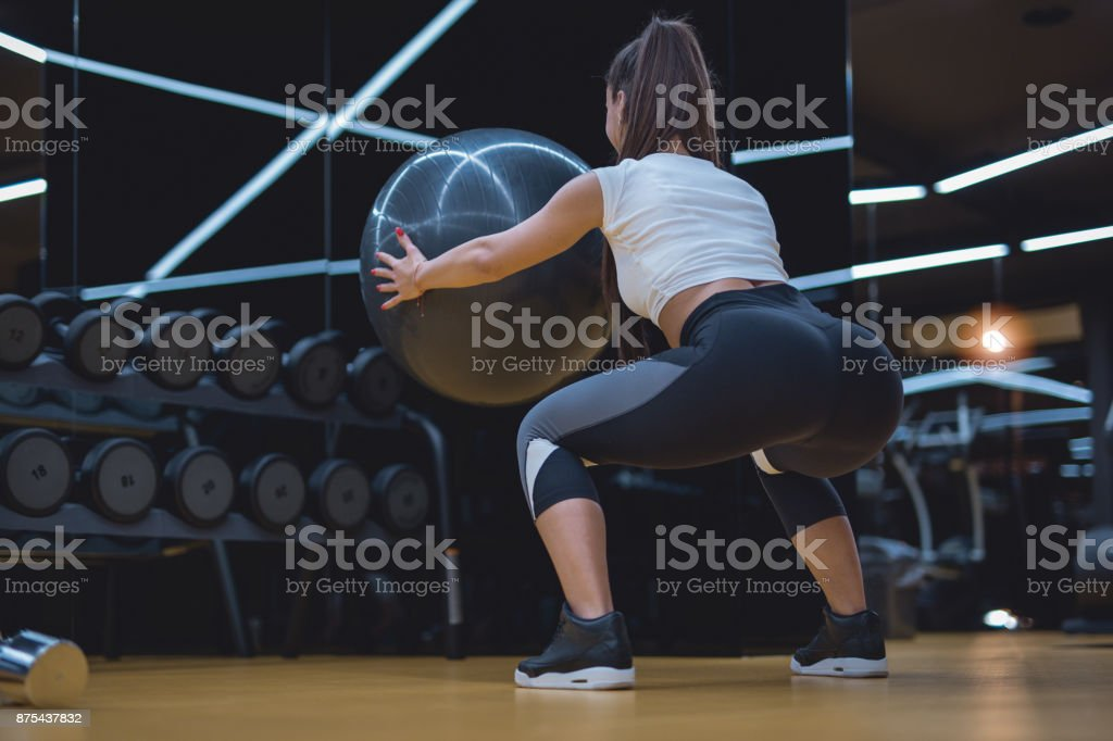 Attractive young woman doing squats at gym stock photo