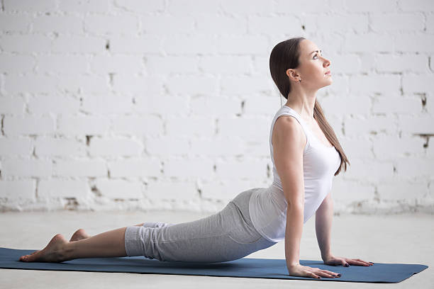 Attractive young woman doing upward facing dog pose Attractive happy young woman working out indoors. Side view portrait of beautiful model doing exercises on blue mat. Standing in upward-facing dog pose, urdhva mukha svanasana. Full length upward facing dog position stock pictures, royalty-free photos & images