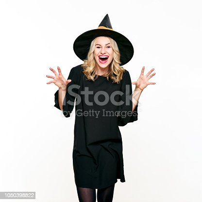 512061362 istock photo Attractive young woman dressed in witch halloween costume isolated over white background. Sensual Halloween Witch Studio Portrait. 1050398822
