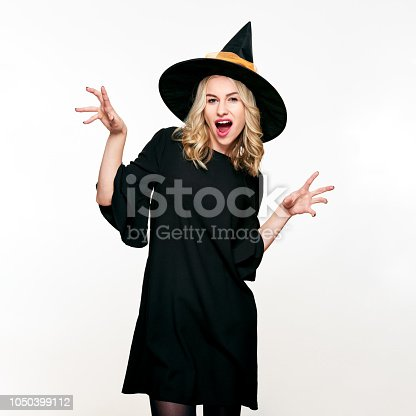 512061362 istock photo Attractive young woman dressed in witch halloween costume isolated over white background. Sensual Halloween Witch Studio Portrait. 1050399112