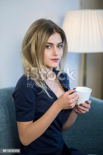 Young business woman drinking coffee and looking at the camera.