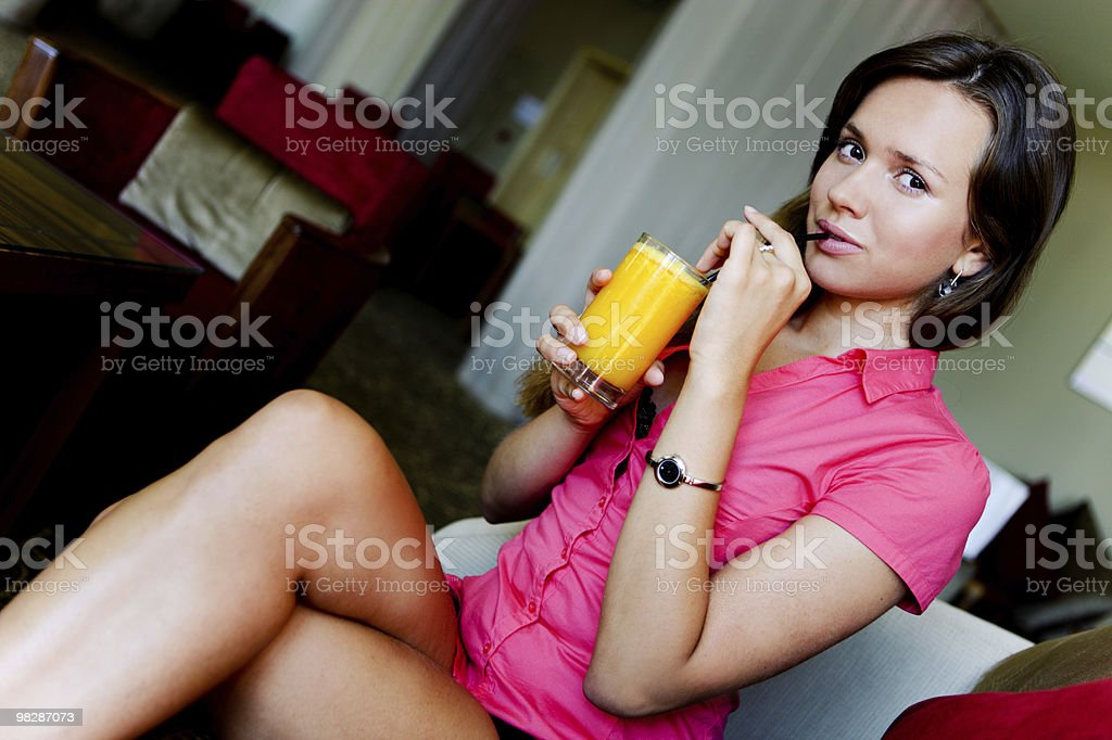 Attractive young woman drinking orange juice royalty-free stock photo