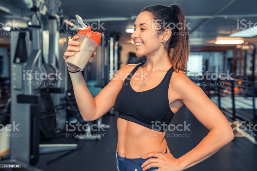 Attractive young woman drinking protein shake at gym stock photo