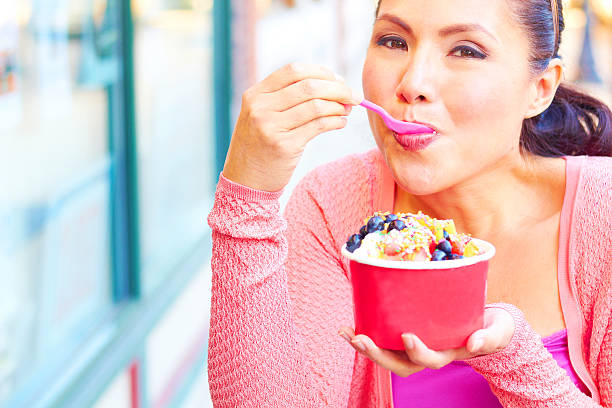 Attractive young woman eating frozen yoghurt stock photo