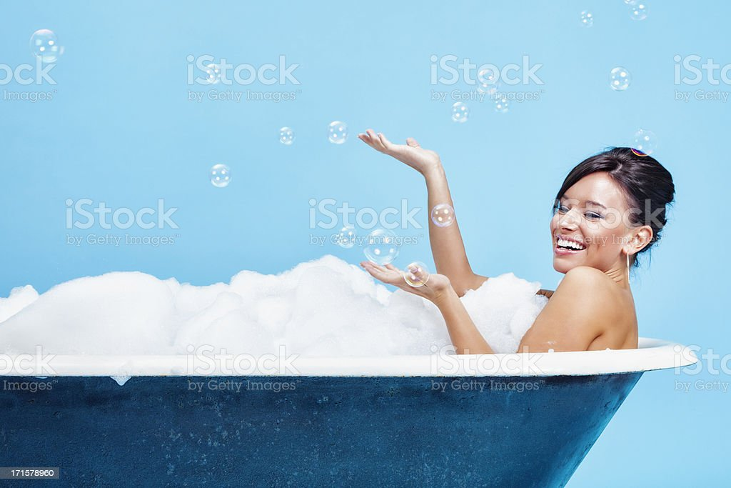 Attractive Young Woman Enjoying a Bubble Bath stock photo