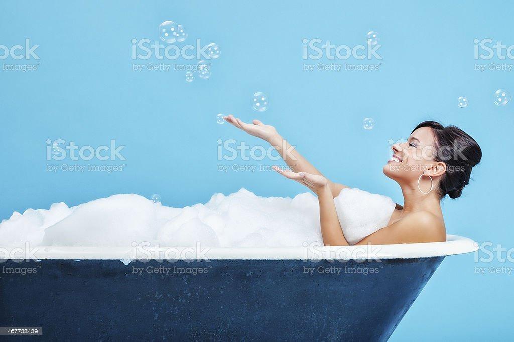 Attraente giovane donna godendo un bagno pieno di schiuma - foto stock
