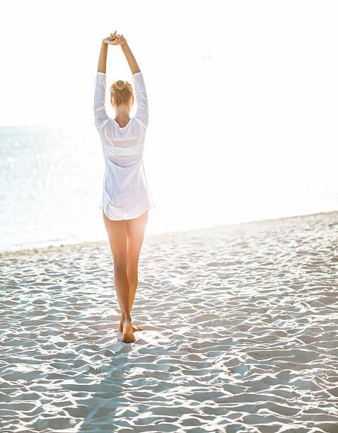 atractiva mujer joven disfrutando de un día en la playa - chica rubia espaldas fotografías e imágenes de stock
