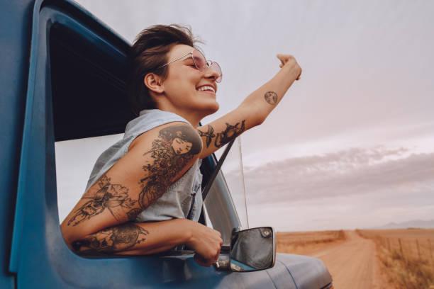 aantrekkelijke jonge vrouw genieten op een road trip - tatoeage stockfoto's en -beelden