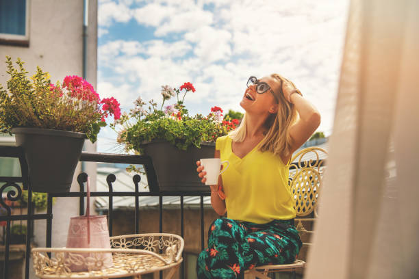 attractive young woman enjoying vacations and drinking coffee on hotel balcony stock photo