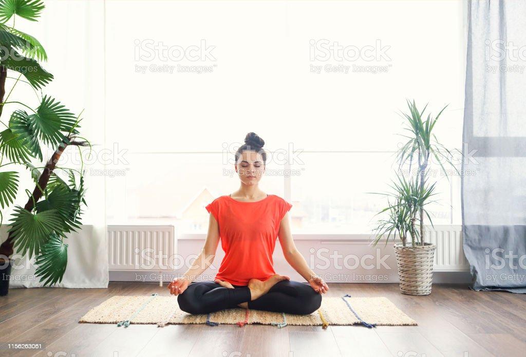 Aantrekkelijke jonge vrouw oefenen en zittend in yoga Lotus positie terwijl rust thuis - Royalty-free 20-29 jaar Stockfoto