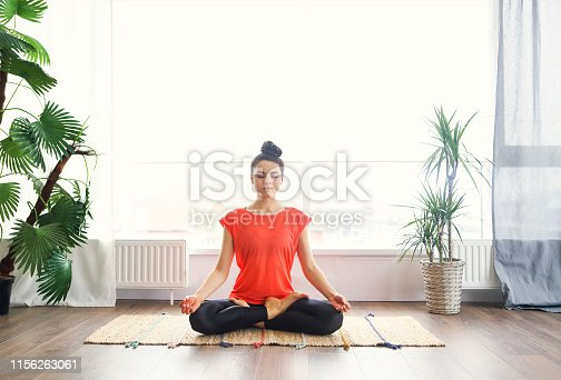 Attractive young brunette woman exercising and sitting in yoga lotus position while resting at home
